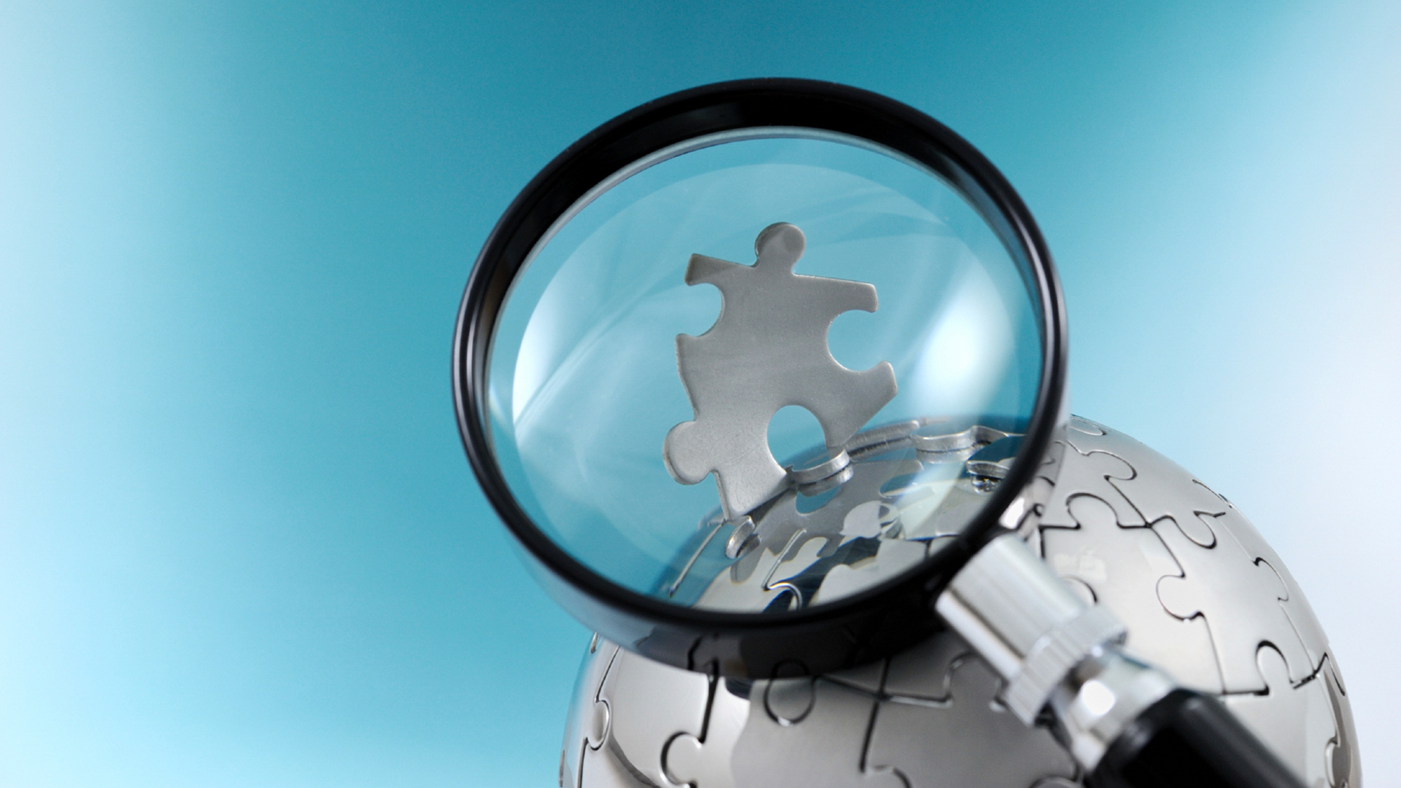 magnifying glass looking at a globe made out of puzzle