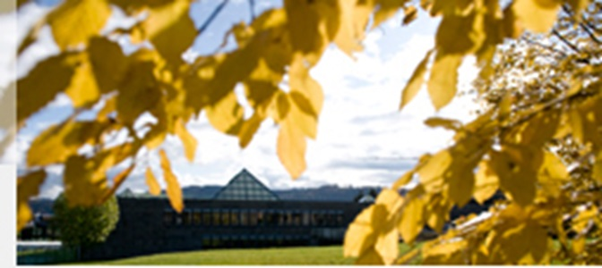 Perspective view of the glass pyramid on top of the Library Building amidst an autumnal scenery.